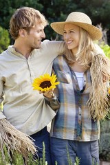 Young couple in scarecrow pose in a field