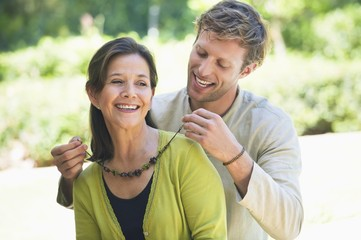 Man fastening mom's necklace outdoors