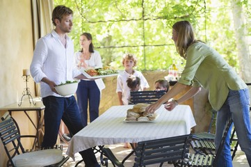 Couple arranging food on dining table with family in the background