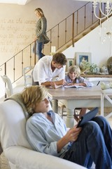 Man talking to little boy with brother using digital tablet in foreground at house