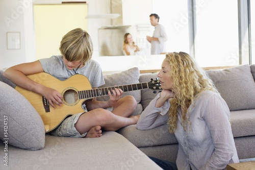 Teenage boy playing a guitar and his mother listening