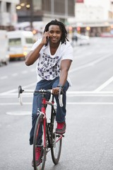 Smiling man talking on a mobile phone while riding a bicycle