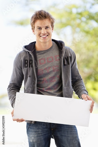 Portrait of a man holding a blank placard