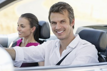 Portrait of a couple driving a convertible car