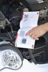 Close-up of a human hand pointing at book while working on broken car engine