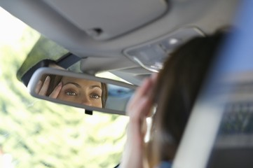 Reflection of a young woman eyes in rear-view mirror