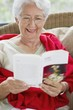 Senior woman reading a magazine and smiling