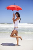 Portrait of a woman holding an umbrella on the beach