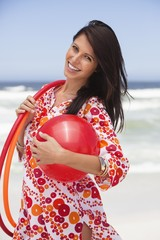 Portrait of a young woman carrying ball and plastic hoops