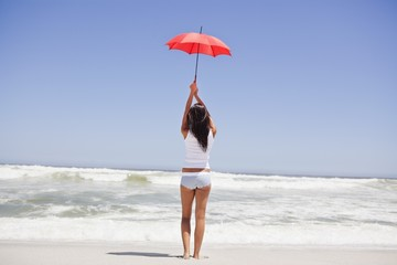Rear view of a woman holding an umbrella on the beach