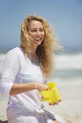 Beautiful woman holding plastic bucket on the beach
