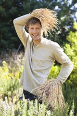 Portrait of a man standing in a field as scarecrow