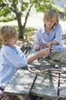 Children making frame of driftwood outdoors