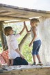 Happy siblings high fiving in tree house