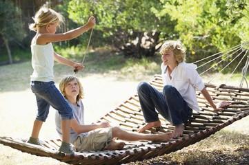 Smiling little siblings playing in hammock