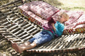 Little girl playing with toy while lying in hammock