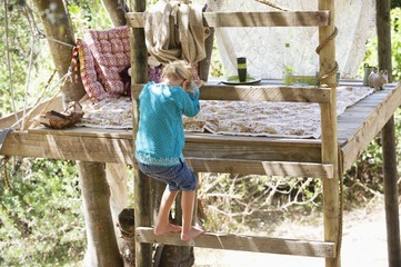 Rear view of a little girl getting down from the tree house