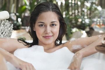 Portrait of a beautiful young woman taking bubble bath