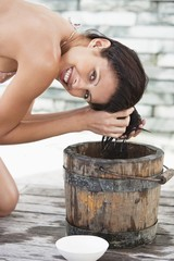 Portrait of a woman washing hair into a bucket