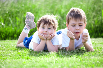 siblings lying on grass