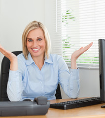 Smiling woman sitting behind desk not having a clue what to do n