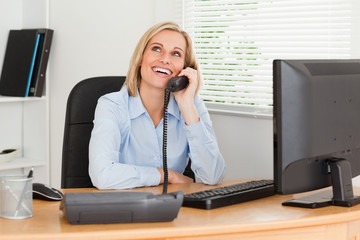 Cheerful businesswoman on phone looking at the ceiling