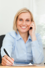 Portrait of a cute businesswoman on mobile noting something look