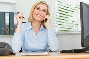 Portrait of a businesswoman smiling at the ceiling with pen in h