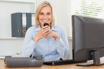 Smiling businesswoman with mobile looking into camera