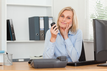Smiling blondebusinesswoman with mobile looking into camera