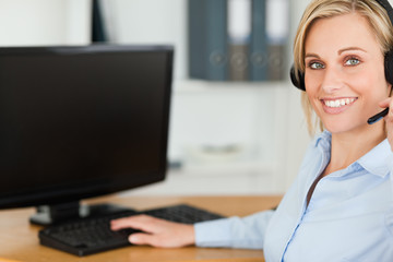 Close up of a blonde businesswoman with headset working with com