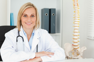 Smiling doctor with model spine next to her