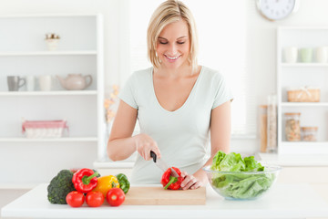 Smiling woman cutting vegetables