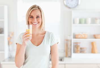 Charming woman holding glass filled with orange juice while stan