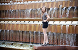 Beautiful young girl standing on edge of big fountain