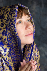 beautiful woman smiling with shawl on head  and praying