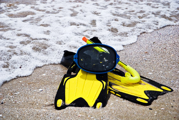 Yellow flippers and swimming mask on the sandy sea beach