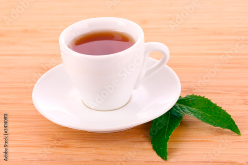 Cup  with mint on wooden background