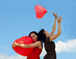 young women holding red balloons against sky