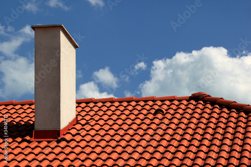 Red tiles roof and chimney with blue sky