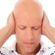 Mann mittleren Alters hält sich die Ohren zu