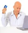 Mann mittleren Alters bestellt mit Kreditkarte im Internet