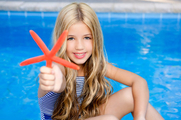 children blond girl in summer vacation pool starfish