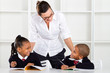 elementary teacher talking to pupils in classroom