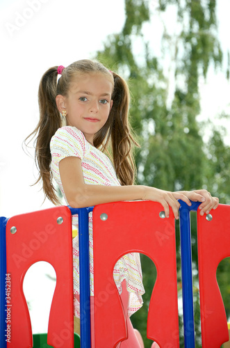 girl standing after a red fence