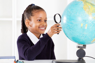 primary schoolgirl looking at globe using a magnifying glass