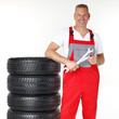 Smiling motor mechanic standing next to a set of winter tyres