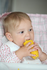 Baby girl eating cooked sweet corn