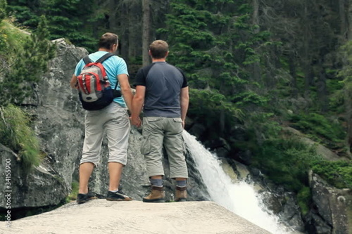 Gay couple holding hands and looking at the beautiful waterfall