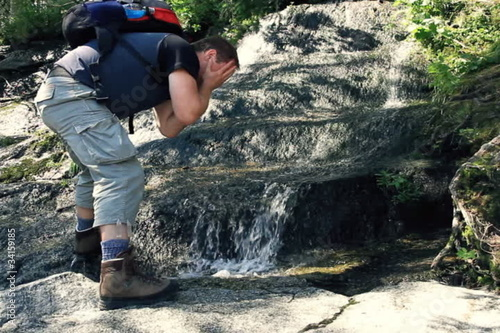 Male hiker washing face, refreshing in the forest stream